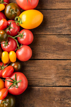 Different tomatoes on rustic wooden background with copyspace. Top view Zdjęcie Seryjne
