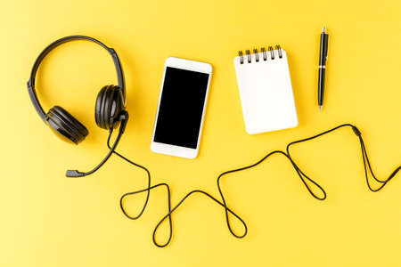 Helpdesk headset with phone, notebook and pen on yellow desktop. Call center