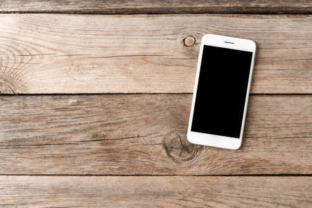 Smartphone with blank screen on wooden table. Top view