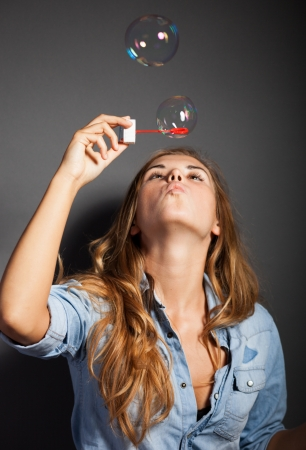 Beautiful young girl blowing soap bubbles on dark background photo