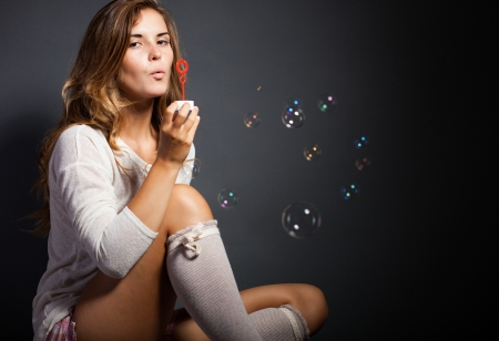 Beautiful young girl wearing socks and blowing soap bubbles photo
