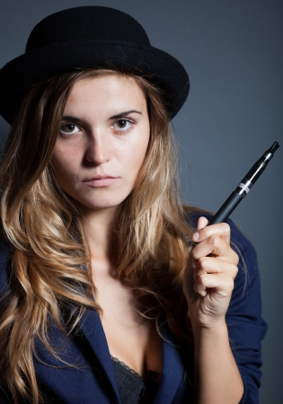 mujer elegante: Elegante mujer sosteniendo y fumar cigarrillo electr�nico