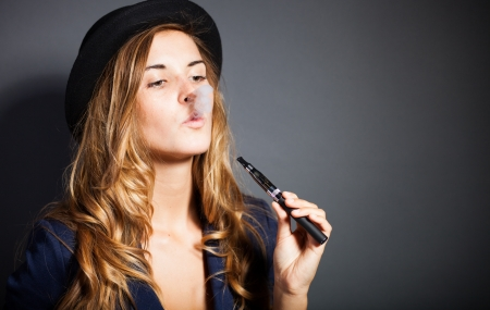 Elegant woman smoking e-cigarette with smoke, wearing suit and hat Stock Photo