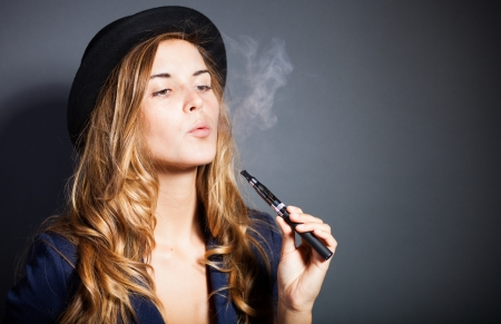 electronic: Elegant woman smoking e-cigarette with smoke, wearing suit and hat Stock Photo