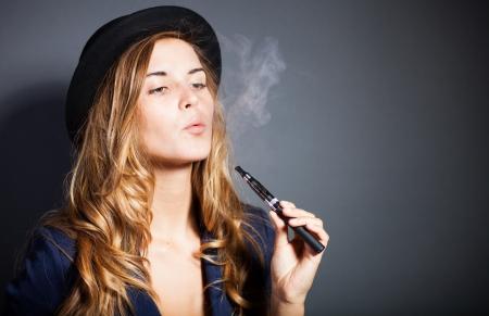 cigarrillos: Mujer elegante de fumar cigarrillo electr�nico de humo, el uso de traje y sombrero