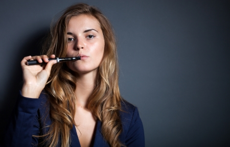 Elegant woman smoking e-cigarette, wearing suit