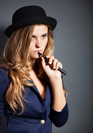 fag: Elegant woman smoking e-cigarette, wearing suit and hat