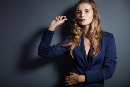 Elegant woman with e-cigarette, wearing suit
