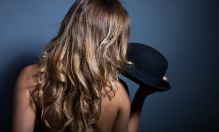 Naked woman standing back holding her hat photo