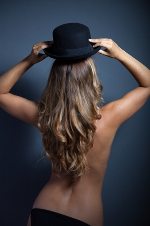 Naked woman standing back wears a hat on her head photo