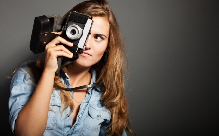 Silly photographer woman holding old camera photo