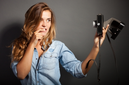 Silly photographer woman taking pictures herself with old camera photo