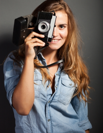 Silly photographer woman taking pictures with old camera photo