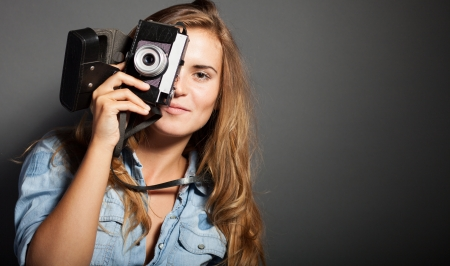 Smiling photographer woman holding old camera photo