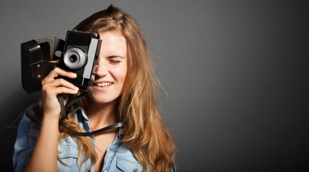 Smiling photographer woman taking pictures with old camera photo