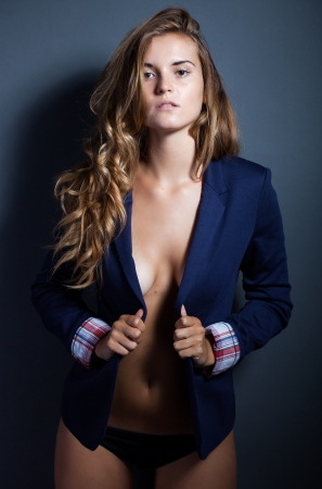 Woman without bra holding her jacket exposing decolletage