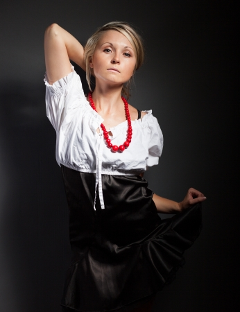 Folk woman in folklore clothes from Europe braiding a plait photo