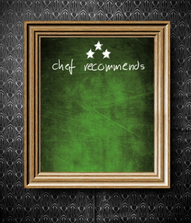 Chef recommends with copy-space chalkboard in old wooden frame on vintage wall photo