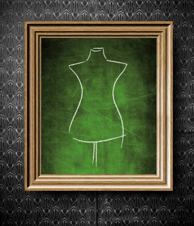 Fashion mannequin sketch chalkboard in old wooden frame on vintage wall photo