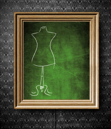 Fashion mannequin sketch with copy-space chalkboard in old wooden frame on vintage wall photo