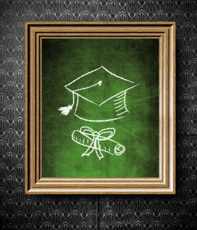 Graduation cap and diploma chalkboard in old wooden frame on vintage wall photo