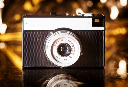Old camera on gold background, vintage style photo