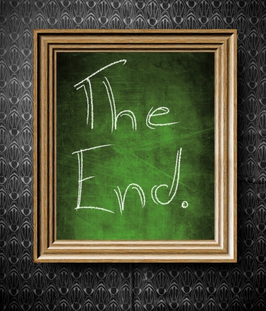 The End symbol chalkboard in old wooden frame on vintage wall photo