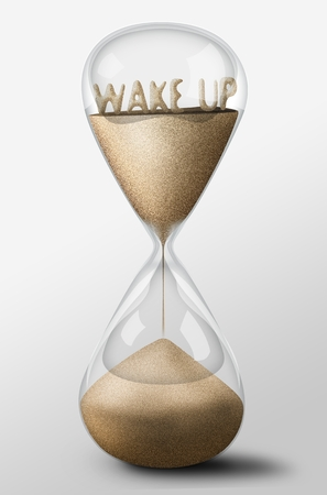 Hourglass with Wake Up word made of sand inside the clock. Concept of work photo