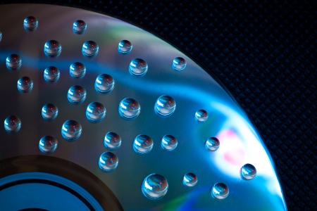 Abstract music background, colorful water drops on CDDVD disc photo