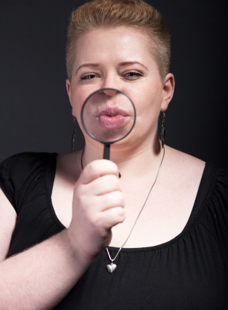 Chubby woman with short hair and magnifying glass blowing a kiss photo