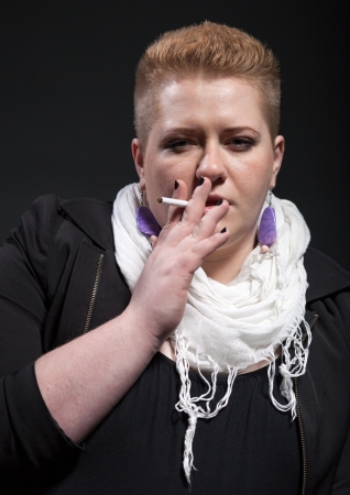 Chubby woman with short hair holding and smoking cigarette photo