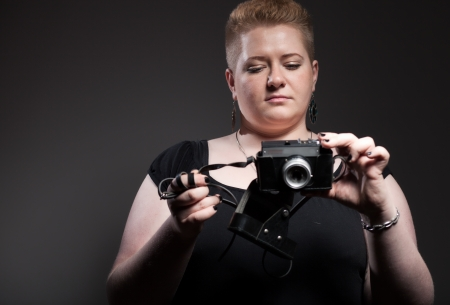 Chubby woman with short hair taking pictures of old camera photo