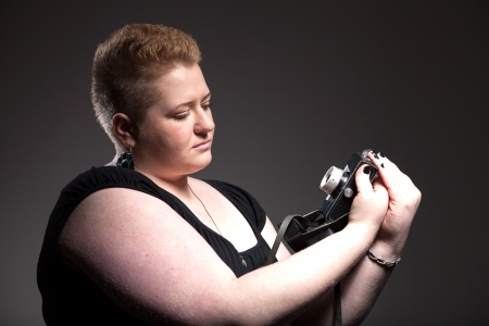 Chubby woman with short hair taking pictures of old camera herself photo