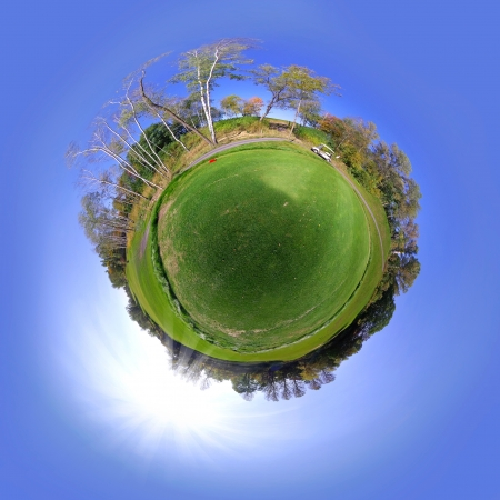 Little tiny planet with grass field and trees, Small world isolated photo