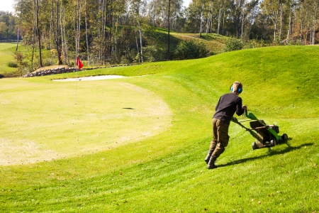Man Mowing Lawn on golf course green using Lawn-Mower