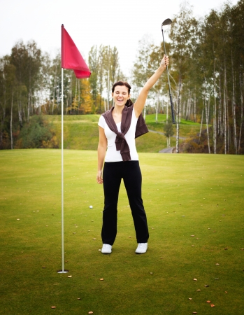 overjoyed: Overjoyed and smiling woman golf player in winner pose on green