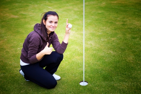 Smiling young woman golf player on green holding ball giving perfect shot sign photo