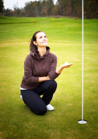 Smiling young woman golf player on green holding ball looking at cup flag photo