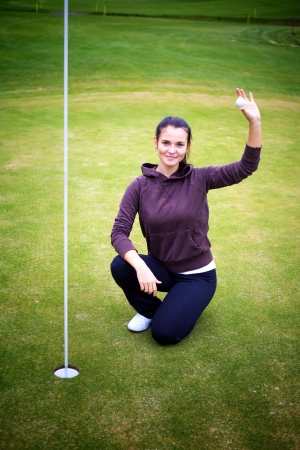 Smiling young woman golf player on green holding ball giving Thumbs Up sign photo