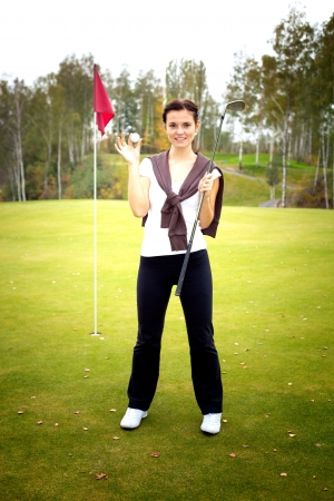 Smiling young woman golf player on green with ball and club near cup flag photo