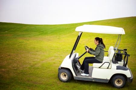 Young woman driving golf cart car photo
