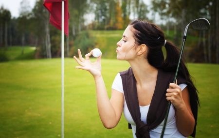 Young woman golf player on green kissing ball photo