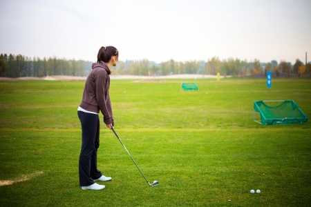 driving range: Young woman player training golf at the driving range