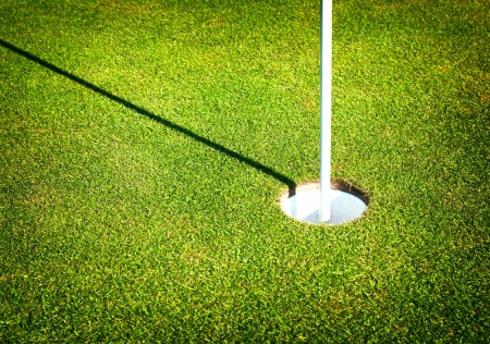 Green grass field of golf course with cup