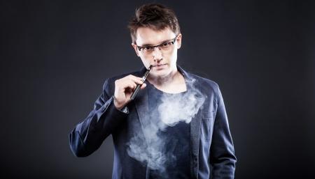 cigarrillos: Hombre joven elegante que fuma el cigarrillo electr�nico