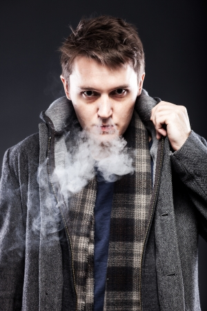 Handsome young man in cigarette smoke photo
