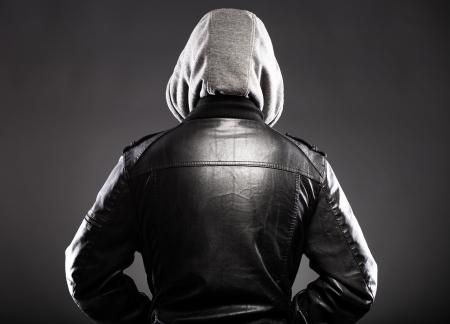 Hombre joven en la chaqueta de cuero y trasera capucha en la espalda