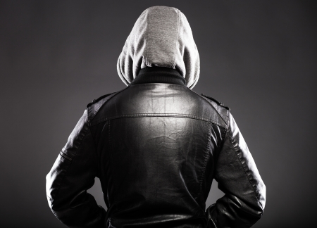 hoodlum: Young man in leather jacket and hood rear view on back Stock Photo