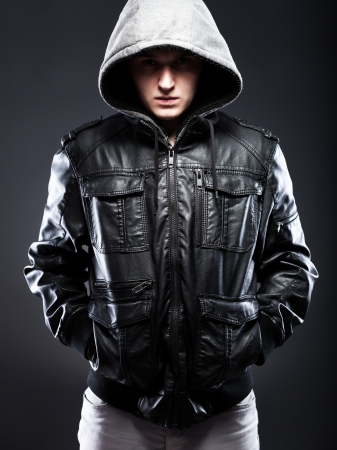 Young man in leather jacket with a hood on darkness background