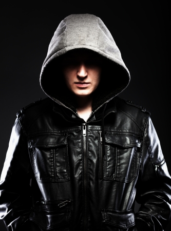 Scary hooligan man in leather jacket with a hood darkness background Stock Photo - 24811295